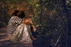 Een vrouw gaat zitten op de houten weg stock afbeeldingen
