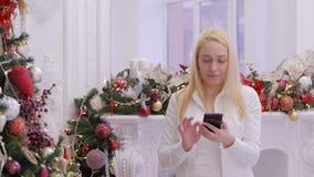 Een vrouw gebruikt een draagbaar gadget aan menings sociale netwerken terwijl het houden van een smartphone in haar handen tegen  stock video