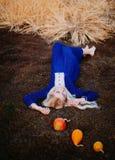 Een vrouw gekleed in een blauwe uitstekende kleding ligt in het de herfstpark stock fotografie
