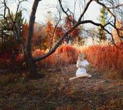 Een vrouw gekleed in een witte kleding met borduurwerk zit Stock Foto