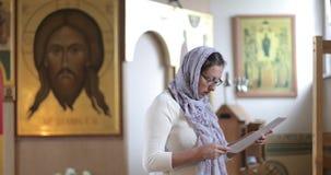 Een vrouw gekleed in sjaal in een Orthodoxe kerk leest een gebed op een blad van document stock footage