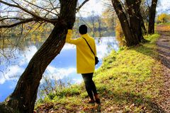 Een vrouw in een gele laag bevindt zich op de kust van een vijver in het landgoed van Telling Leo Tolstoy in Yasnaya Polyana Royalty-vrije Stock Fotografie