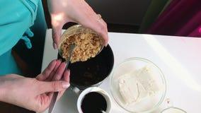Een vrouw giet kruimelkoekjes met boter in de vorm voor kaastaart stock video