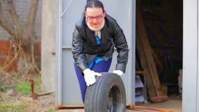 Een vrouw in glazen ontwikkelt een autoband met een schijf uit de garage stock footage