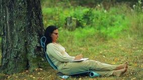 Een vrouw in glazen zit blootvoets onder een boom in het park en trekt een potlood in een notitieboekje stock videobeelden