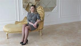 Een vrouw in grijze bedrijfskleding zit op een gouden uitstekende laag stock footage