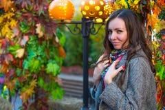 Een vrouw in een grijze laag en gekleurde sjaal in de herfst in Moskou stock foto