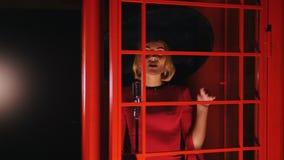 Een vrouw in grote retro hoed en het rode kleding zingen achter de rode glasdeur stock videobeelden