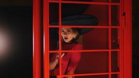 Een vrouw in grote retro hoed en rode kleding keert zich om en begint achter de glasmuur te zingen stock footage