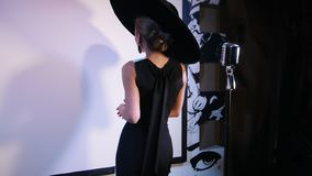 Een vrouw in grote retro hoed en zwart-witte kleding die prestaties op het stadium hebben Draaien aan het publiek en het begin stock footage