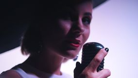 Een vrouw in grote zwarte elegante hoed grijpt mic en begint te zingen stock footage