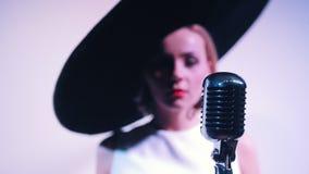 Een vrouw in grote zwarte elegante hoed loopt aan mic en begint te zingen stock footage