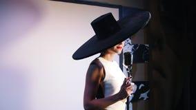 Een vrouw in grote zwarte hoed loopt aan mic en begint te zingen stock videobeelden