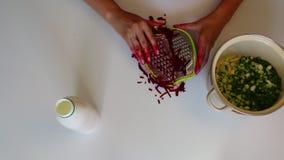 Een vrouw hakt gekookte bieten op een plantaardige rasp Naast de pan zijn andere ingrediënten voor groentesoep stock video
