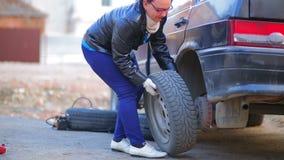Een vrouw in handschoenen verwijdert een band op een schijf uit een auto stock footage
