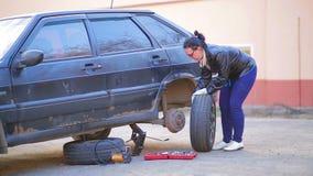 Een vrouw in handschoenen zet een band op een schijf op de as van een auto stock video