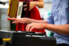 Een vrouw een harmonika spelen en een man die het toetsenbord spelen stock fotografie