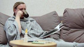 Een vrouw heeft thuis een koude Liggend op de laag met een boek, met een deken wordt behandeld die stock footage