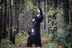 Een vrouw in een heksenkostuum in een bos stock afbeeldingen