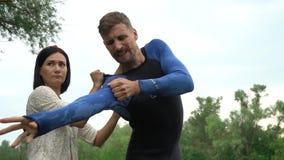 Een vrouw helpt een man om een vrij duiken uit te rusten stock video