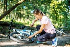 Een vrouw herstelt wiel van een fiets Het concept het cirkelen en a Royalty-vrije Stock Fotografie