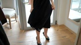 Een vrouw in hielen in een zwarte lange kledingsdraaien rond zich stock footage