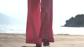 Een vrouw in hoge hielen loopt langs de strandboulevard in langzame motie stock video