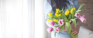 Een vrouw houdt een boeket van verse tulpen De bloemen zijn geel en roze Het meisje door het venster Plaats voor tekst royalty-vrije stock afbeelding