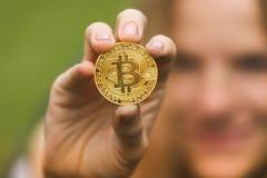 Een vrouw houdt een gouden muntstuk bitcoin in haar handen Royalty-vrije Stock Foto's