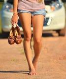 Een vrouw houdt haar schoenen en gang Stock Foto