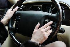 Een vrouw houdt het stuurwiel van een luxeauto stock foto's
