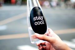 Een vrouw houdt een platic fles met water openlucht Royalty-vrije Stock Afbeelding