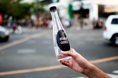 Een vrouw houdt een platic fles met water openlucht Stock Afbeelding