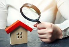 Een vrouw houdt een vergrootglas over een blokhuis Onroerende goederenschatter Beoordeling van de voorwaarde van het huis stock foto's