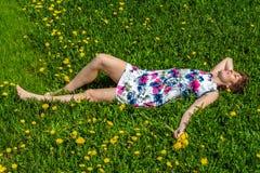 Een vrouw in een katoenen kleding ligt op het groene gras met paardebloemen royalty-vrije stock foto's