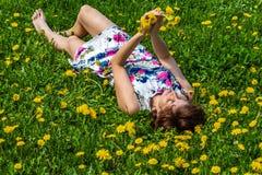 Een vrouw in een katoenen kleding ligt op het groene gras met paardebloemen stock fotografie