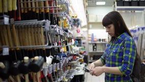 Een vrouw kiest een hamer in een opslag van bouwgoederen