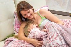 Een vrouw koestert weinig dochter in bedontwaken royalty-vrije stock fotografie