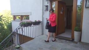 Een vrouw komt uit de deur stock videobeelden