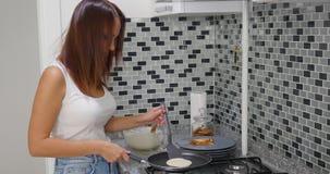 Een vrouw kookt in een keukenbrand stock afbeelding