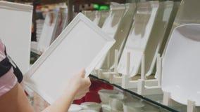 Een vrouw koopt schotels in de opslag, onderzoekt diverse punten van schotels stock videobeelden