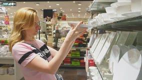 Een vrouw koopt schotels in de opslag, onderzoekt diverse punten van schotels stock video