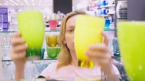 Een vrouw koopt schotels in de opslag, onderzoekt diverse punten van schotels stock footage