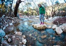Een vrouw kruist een stroom Stock Foto