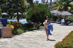 Een vrouw in kuuroordtoevlucht in zwemmend kostuum die zonbaden nemen Stock Afbeelding