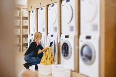 Een vrouw laadt de bladen in de te wassen en te drogen wasserij stock foto