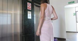 Een vrouw in een lange kleding met een koffer veroorzaakt een lift in de zaal stock videobeelden