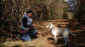 Een vrouw leidt een jonge hond op stock video