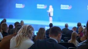 Een vrouw let op een seminarie en luistert aan de spreker Bespreek het concept economische ontwikkeling en nieuwe technologieën stock footage