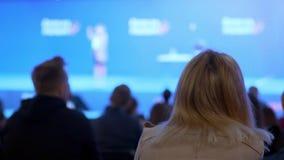 Een vrouw let op een seminarie en luistert aan de spreker Bespreek het concept economische ontwikkeling en nieuwe technologieën stock video
